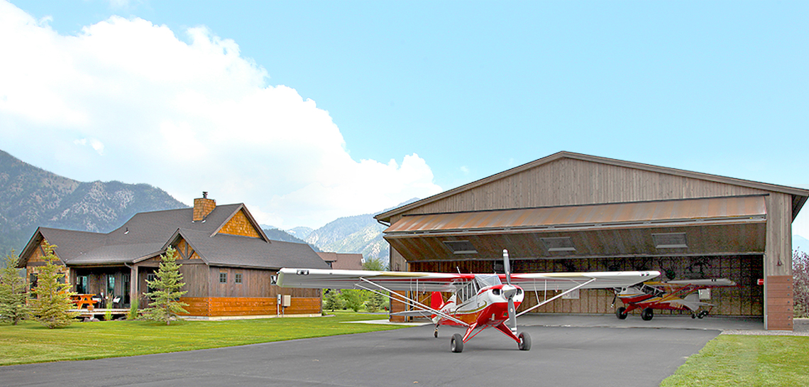 red and white plane in front of bifold door on a hangar